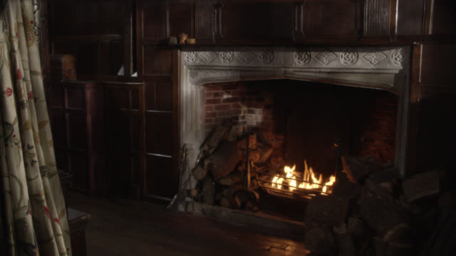 medium angle of fire burning in fire place. bed curtains visible. wood logs stacked near fireplace. wood paneled wall. - fireplace stock videos and b-roll footage