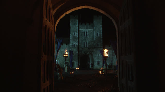 wide angle of castle through arched doorway or entrance. torches and banners visible. could be tower of london. location is actually knole castle, sevenoaks, kent. stone buildings. - castle stock videos & royalty-free footage