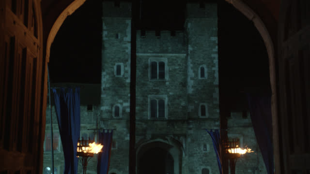 zoom in on castle through arched doorway or entrance. torches and banners visible. could be tower of london. location is actually knole castle, sevenoaks, kent. stone buildings. - schlossgebäude stock-videos und b-roll-filmmaterial