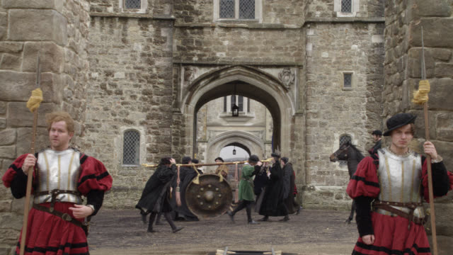 medium angle of soldiers or guards with armor and axes guarding entrance to castle. stone building with arches. priests in black robes in bg. could be courtyard. - courtyard stock videos & royalty-free footage