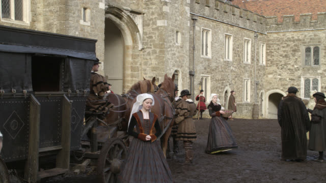 wide angle of renaissance townsfolk, villagers, people of the court and servants in muddy courtyard of stone building with crenellation or castle. knole at sevenoaks in kent. horse-drawn carriage. - courtyard stock videos & royalty-free footage