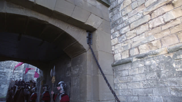 wide angle moving pov through tunnel or archway to crowd of upper class people in courtyard. renaissance nobility or gentry. stone building with crenellation or castle in bg. could be tower of london, actually dover castle. - courtyard stock videos & royalty-free footage