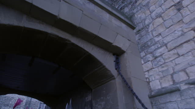 up angle moving pov through tunnel or archway to crowd of upper class people in courtyard. renaissance nobility or gentry. stone building with crenellation or castle in bg. could be tower of london, actually dover castle. - courtyard stock videos & royalty-free footage