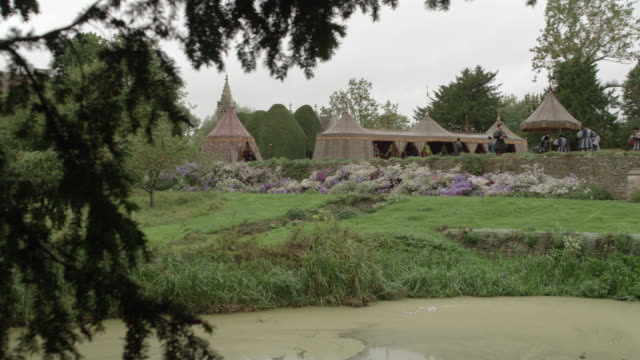 pan up from pond to tents in garden for party or celebration. could be wedding. renaissance. trees and flowers. manor house, great chalfield, wiltshire, england. - renaissance stock-videos und b-roll-filmmaterial