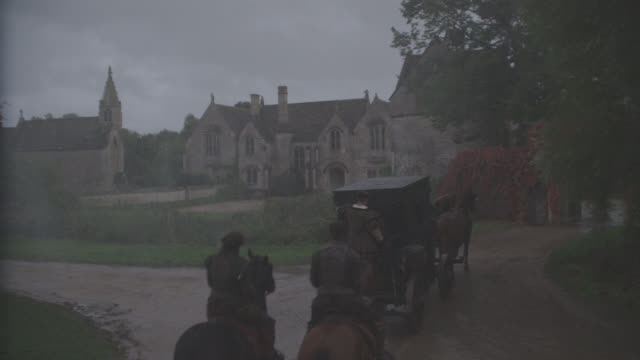 vidéos et rushes de pan up from horse-drawn carriage arriving at upper class house or mansion. could be estate. chapel or church. raining. manor house in great chalfield, wiltshire, england. countryside. - voiture attelée