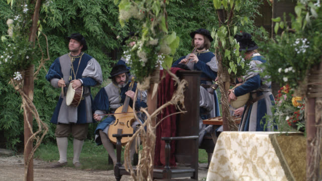 wide angle of band of renaissance musicians playing instruments. upper class people, nobility, gentry or royalty walking through gardens. could be celebration or party. - stereotypically upper class stock videos & royalty-free footage
