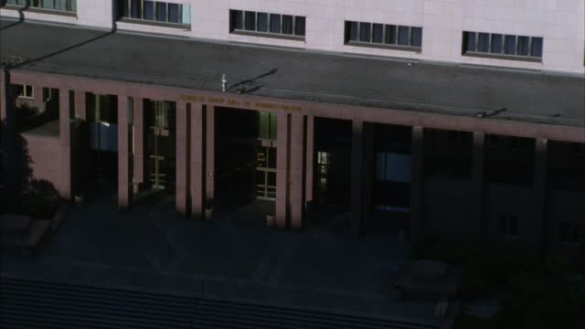 aerial of kenneth hahn hall of administration in downtown los angeles. could be government building. camera pulls back to reveal wide angle of downtown. los angeles city hall. mountains and house in bg. office buildings in fg. - 1980 stock videos & royalty-free footage