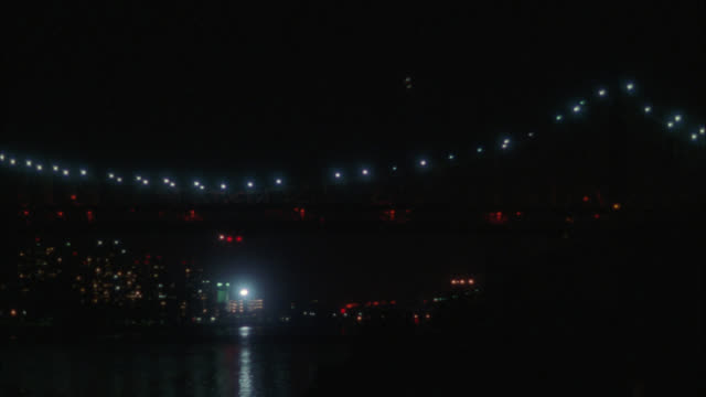 pan right to left of queensboro bridge over east river. white lights on suspension cables visible. high rise office or apartment buildings in bg. - queensboro bridge stock videos & royalty-free footage
