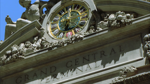 "pan down on statue and clock above entrance to grand central station in new york. inscription on building reads ""grand central terminal"". clock reads 12:15. train stations. - grand central station manhattan stock videos & royalty-free footage"
