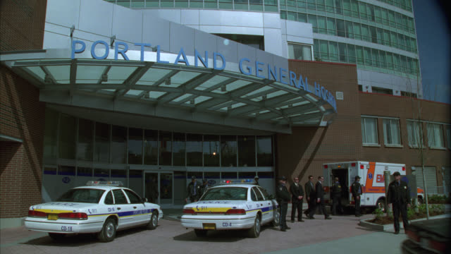 """wide angle of police motorcycle and police car with bizbar, flashing lights pulling up to entrance of modern hospital building and parking next to second police car and ambulance. sign above entrance reads """"portland general hospital"""". cops. police officer - portland oregon stock-videos und b-roll-filmmaterial"""