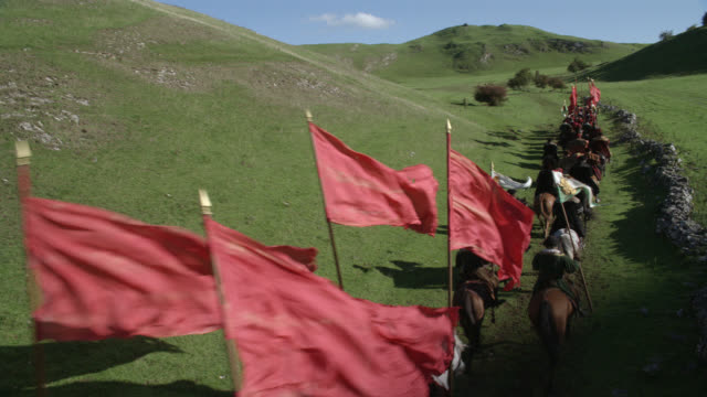 wide angle of renaissance guards on horseback and holding flags across english countryside or hillside. could be royal procession or escort. view from rear. hills or meadow, rocks, shadows visible. blue sky. - royal blue stock videos & royalty-free footage