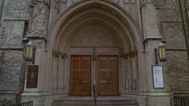 medium angle of entrance to church, chapel, or cathedral. could be catholic school. arched doorway. religious sculptures or relief over wooden doors. winter. bare branches on trees. - catholicism stock videos & royalty-free footage