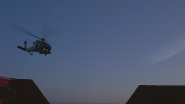 WIDE UP ANGLE OF HELICOPTER FLYING FROM DISTANCE TOWARD CAMERA OVER BUILDINGS THAT COULD BE WAREHOUSES. DUSK. SHOT PANS RIGHT AS HELICOPTER FLIES RIGHT OVER AND HOVERS OVER GROUND. NINE PEOPLE SLIDE DOWN ROPE HANGING FROM HELICOPTER ONE BY ONE TO GROUND.