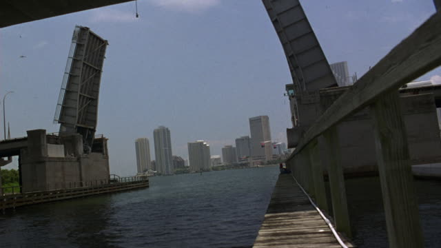 wide angle of two helicopters flying over marina towards open drawbridge. downtown miami skyline visible in background. harbor water visible in foreground. - drawbridge stock videos and b-roll footage