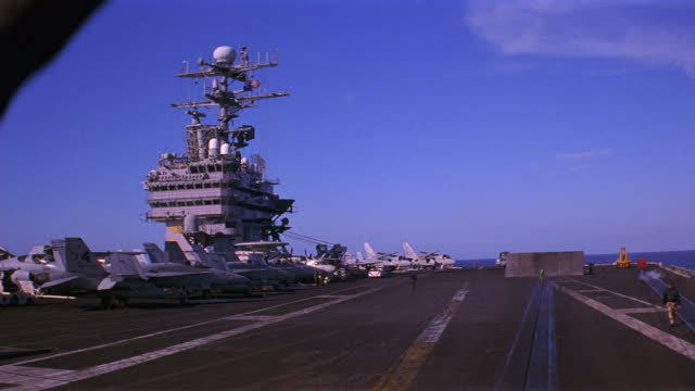 PAN UP OF DECK NAVY AIRCRAFT CARRIER. BLAST SHIELD RAISED. FA-18 HORNET FIGHTER JETS, E-2C HAWKEYE PROPELLER PLANES, AND S-3B VIKING JETS PARKED AND SECURED TO DECK. BRIDGE, RADAR ANTENNAS AND CONNING TOWER VISIBLE. MILITARY PERSONNEL MOVE AND WORK ON DEC