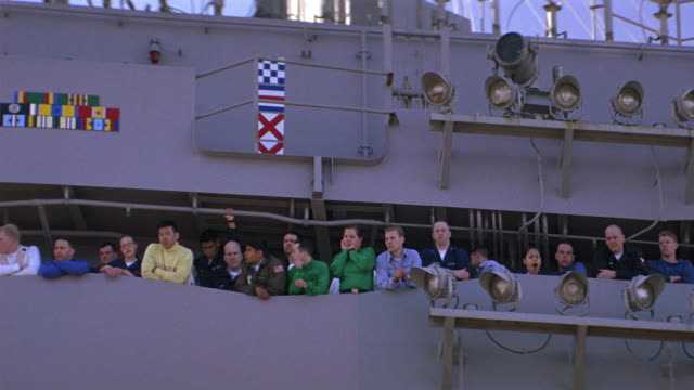 medium angle of sailors or military personnel on aircraft carrier or navy ship watching something off screen. - marinaio video stock e b–roll