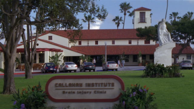 """wide angle on a building sign in fg reading """"callahan institute brain injury center."""" a spanish style medical center in bg with a white statue on lawn in front of building. - medical building stock videos and b-roll footage"""