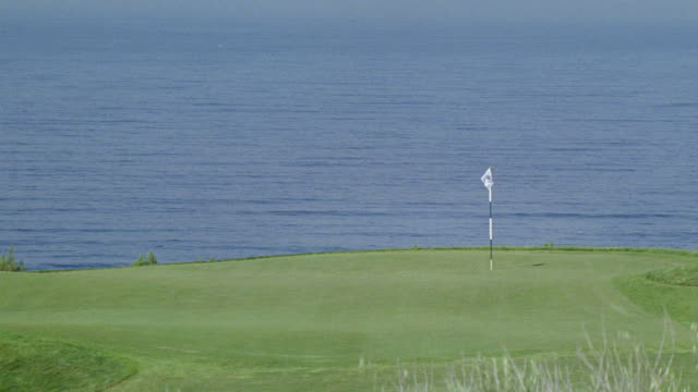 wide angle. est golf hole. flag on far side of green. parts of apron visible. ocean water in bg behind hole. golf balls fall onto green. - golf flag stock videos and b-roll footage