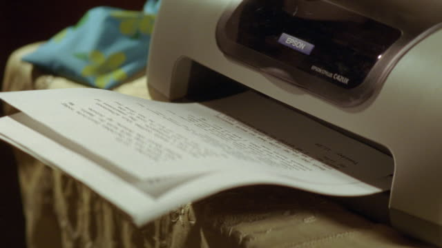 insert of gray and black epson printer printing out words on white computer paper. printer on table. - printing out stock videos and b-roll footage