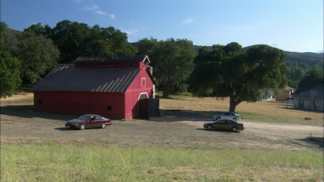 ws. est traditional looking red  barn with cars parked outside. trees around it. - barn stock videos & royalty-free footage