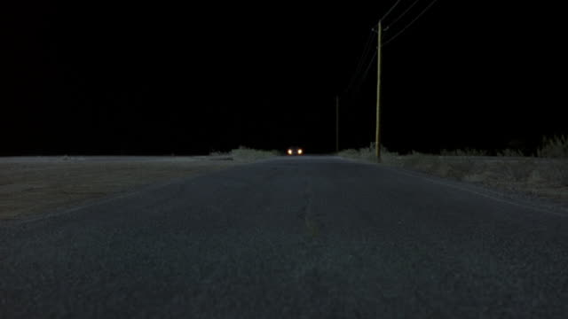 medium angle of 1980's beige mercedes driving on rural desert highway at night toward camera. 1969 red dodge charger and what could be blue ford bronco pass camera, driving in opposite direction. the two cars swerve to opposite sides to avoid the mercedes - 1980 stock videos and b-roll footage