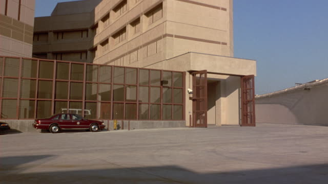 "vídeos y material grabado en eventos de stock de wide angle of blue car entering gate of large multi-story concrete prison or jail. gates close behind car. high metal fence frame left. location is los angeles county sheriff's ""twin towers correctional facility"" near downtown l.a. jails. - puerta estructura creada por el hombre"
