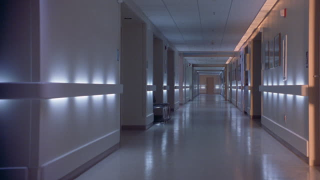 stockvideo's en b-roll-footage met medium angle of long hallway. could be hallway of medical center, hospital, or building. see fluorescent lights along walls of hallways. - gang