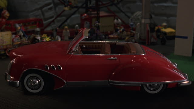 medium angle of red remote control convertible car facing frame left. see driver door open and close. see various toys in background. could be in child's bedroom or playroom. - ラジコン点の映像素材/bロール