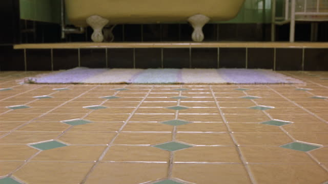 medium angle of peach and teal bathroom floor. see rug and yellow bathtub in background. see black and green tile on walls. - bathroom stock videos & royalty-free footage