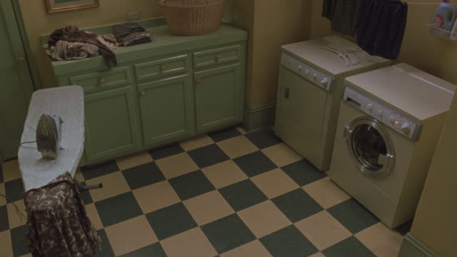 high angle down of laundry room. see yellow washer and dryer to frame right. see pastel green cabinets with clothes and laundry basket on top against far wall. see ironing board with article of clothing draped across top.  see yellow and green checkered f - 1999 stock videos & royalty-free footage