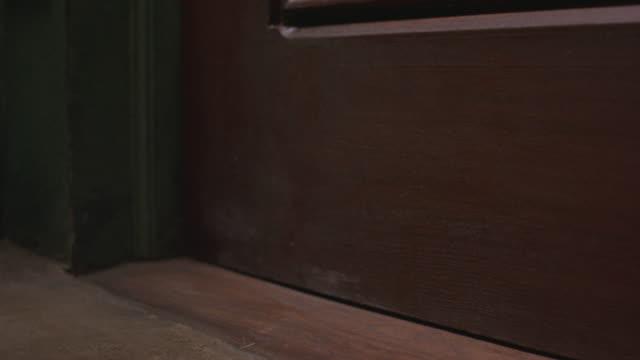 close angle of bottom corner of door. see brown wooden door, molding of green wall and floor. - door stock videos & royalty-free footage