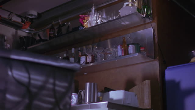 up angle of kitchen or bar. see shelves filled with beer bottles and wine bottles in foreground. see black figure with wires on left, could be television. see refrigerator on right. see gunshots or gunfire and hit alcohol bottles. see glass shatter. - black entertainment television stock videos & royalty-free footage