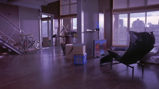 medium angle of loft or multi-level apartment. see large  white windows emitting outside light into loft. see high rise buildings through windows. see white staircase on left. see white and yellow bicycle next to staircase. see entrance to other room in b - black entertainment television stock videos & royalty-free footage