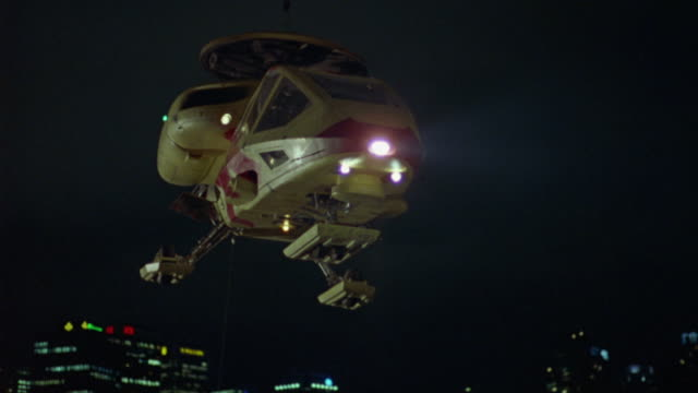 medium angle of futuristic helicopter or 'whispercraft.'  vehicle. bullets, shots hit helicopter, explosion, flames, fire. vehicle falls. cityscape visible in background. heli-pads. - unfall konzepte stock-videos und b-roll-filmmaterial