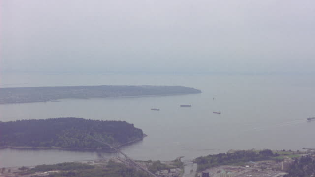 AERIAL OF BAY. BARGE OR SHIP, CITY OF VANCOUVER SEEN. DESCENDING ONTO HELICOPTER LANDING PAD. HELI-PADS.
