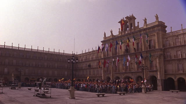 wide angle of plaza or courtyard in europe. crowd or people stand waving spanish flags and cheering. plaza center. international flags hang. camera pulls back as crowd flees suddenly. plaza mayor. people running. - courtyard stock videos & royalty-free footage