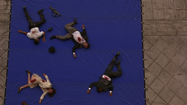 vídeos y material grabado en eventos de stock de high angle down of bleeding, wounded people lying on ground. victims. men and woman wearing business attire. could be businesspeople. police officer, security or armed guard near gun crawls towards woman. could be dead bodies. blue screen. - moving image