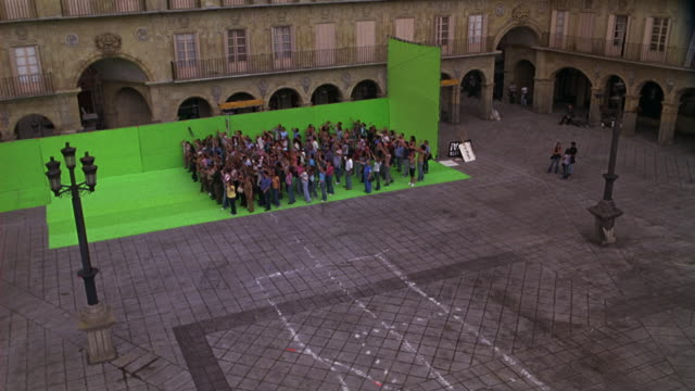 vídeos de stock e filmes b-roll de pan up, medium angle of crowd of people cheering or protesting in plaza courtyard against green screen. plaza mayor, europe. could be for protest or rally. - imagem em movimento