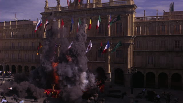 wide angle of explosion of stage and people in front of plaza mayor or courtyard. flags hang from building. disaster. accidents. could be for rally or political event. smoke. - courtyard stock videos & royalty-free footage