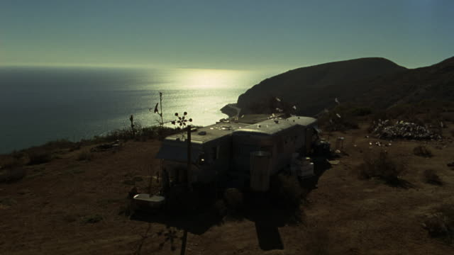 high angle down of a mobile home in a trailer park in the mountains above malibu.  could be any coast along the pacific ocean in california.  looks like a vacation home on the coastline. pacific coast. - trailer home stock videos & royalty-free footage