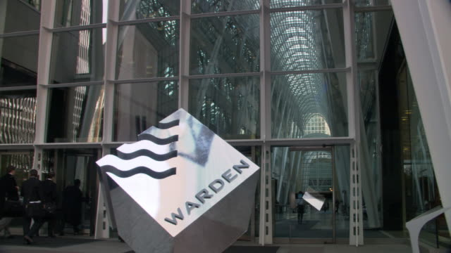 """WIDE ANGLE OF OFFICE BUILDING WITH REVOLVING DOORS IN LOBBY, MULTI-STORY ATRIUM. METAL CUBE SCULPTURE SIGN MARKS BUILDING AS """"WARDEN"""" INDUSTRIES OR BUSINESS. MEN ENTERING AND EXITING BUILDING. LOCATION IS 1 KING WEST, TORONTO. MATCHING DX 2841-045 TO 2841"""