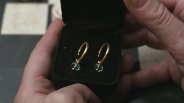 close angle of hands of man opening ring box revealing gold ear rings with jade colored beads. closes box. chess board in bg. jewelry. - jewelry box stock videos and b-roll footage