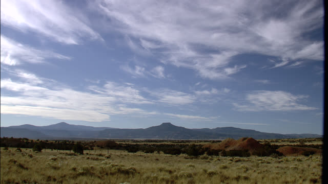 wide angle of grasslands with plateau mountains in bg. blue skies with some clouds. abiquiu. ghost ranch. taos new mexico. - new mexico stock videos & royalty-free footage