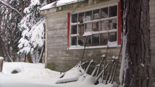 medium angle of old or abandoned shack, house, shed, or  cabin with shovels resting against building. shovels partially covered by snow. window on side of house. snow falls from sky. trees in bg. - cabin stock videos & royalty-free footage