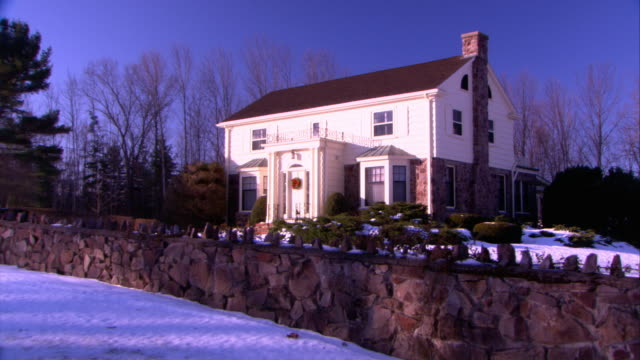 wide angle of colonial revival style house with stone fence in front. snow on ground. brick and siding on house. trees bare in bg. could be rural area. - brick house stock videos & royalty-free footage