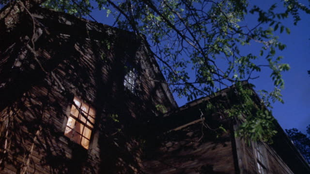 UP ANGLE OF SIDE OF TWO STORY CABIN HOUSE WITH ATTIC. SEE LIGHT SHINING THROUGH SECOND STORY WINDOW. SEE TREE BRANCH OVERHANGING FROM LEFT.