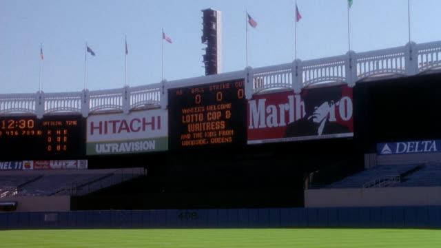 """stockvideo's en b-roll-footage met wide angle of electronic scoreboard in empty yankee stadium. see ads next to scoreboard above bleachers. flags line the stadium. scoreboard reads """"yankees welcome lotto cop & waitress"""". - scorebord"""