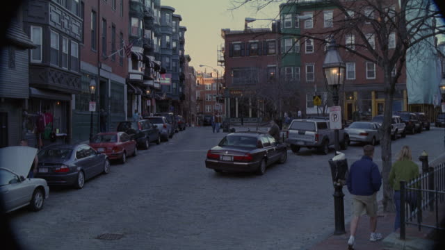 "wide angle of boston neighborhood, multi-story wood paneled and brick  apartment buildings with shops, cars parked on street, ""no parking"" sign, men and women walking. new england. - boston stock videos and b-roll footage"