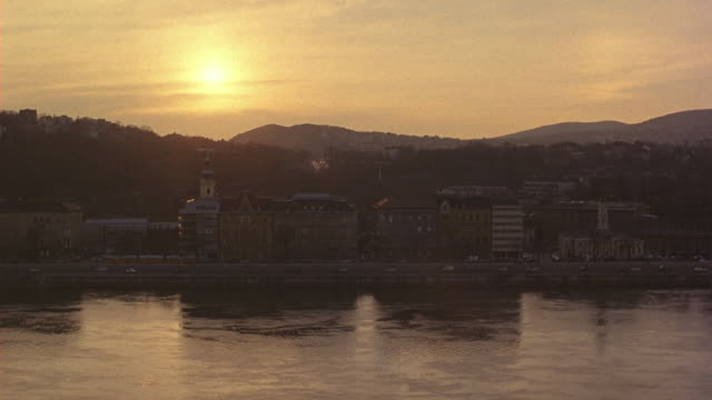 vídeos de stock, filmes e b-roll de wide angle of danube river at sunrise. apartment or commercial buildings line the river bank. traffic visible on the roads alongside river. - hungria