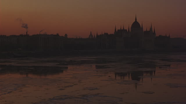 pull back from hungarian parliament building and reflection in river to reveal sunrise behind budapest city skyline. large hotel on river bank. chimney smoke rises into orange and purple sky.  ice floats on danube river in fg. - budapest video stock e b–roll
